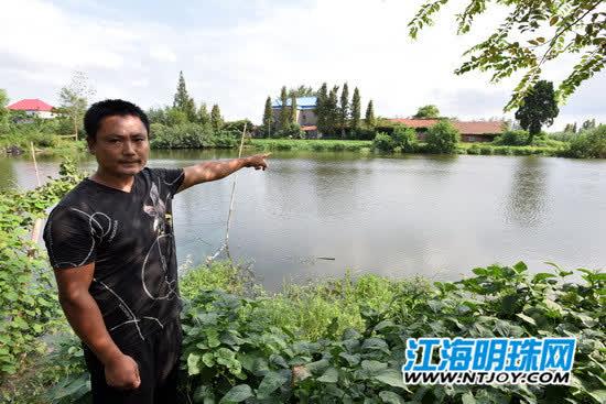 陈怀远站在河塘边回忆救人的过程.jpg